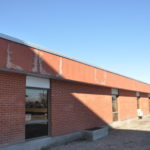 Photo of High School exterior showing crumbling roof.